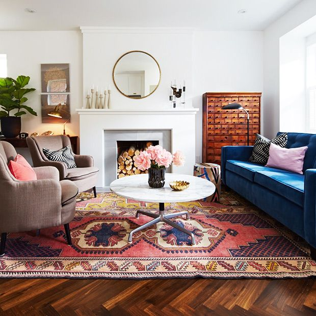 While the shape of the couch is fairly mod, its color is fresh and funky. The pops of pink are not only youthful and vivid but the bold rug layered on top of herringbone flooring takes the formality down.