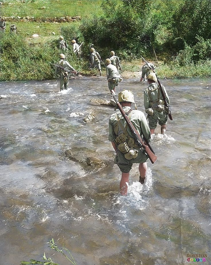 Holding their trousers high, marines ford a stream while on patrol in the 'Punchbowl Valley' area of the eastern front in Korea on Sept. 5, 1951. (Colourised by Royston Leonard)