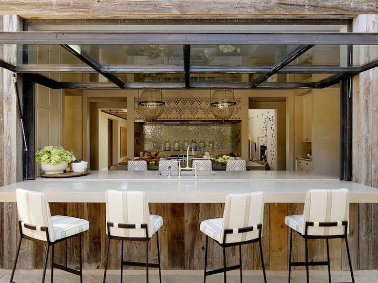 Patio kitchen pass through boasts reclaimed wood plank walls framing an outdoor bar lined with iron barstools with striped cushions under a metal and glass fold down window.