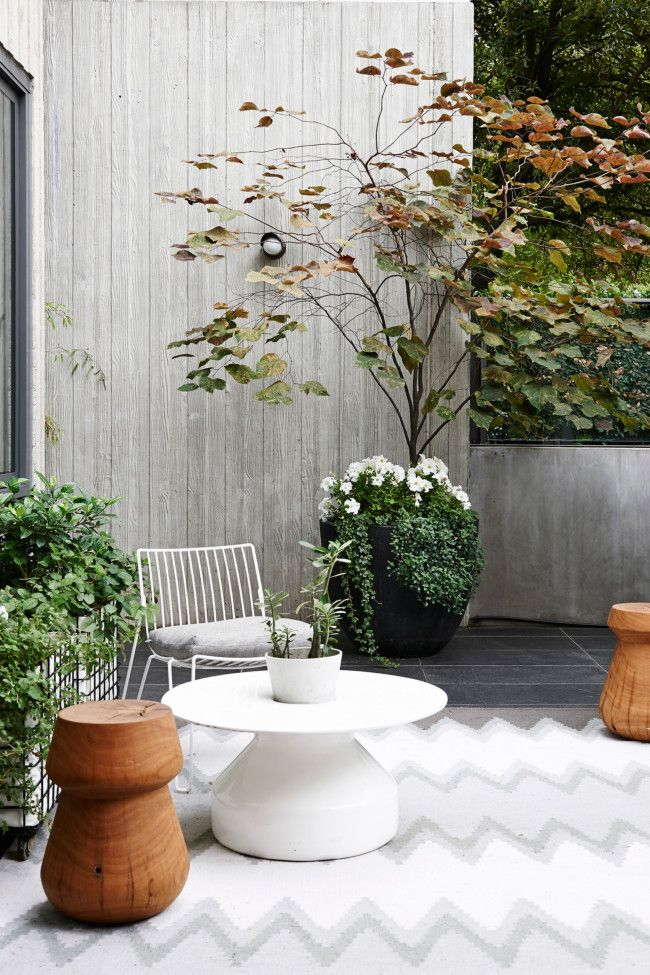 On the terrace, 'Stanley' side tables by Jardan and a 'TIO Lounge Chair' from Luke Furniture sit on an indoor/outdoor rug from West Elm. Pla...