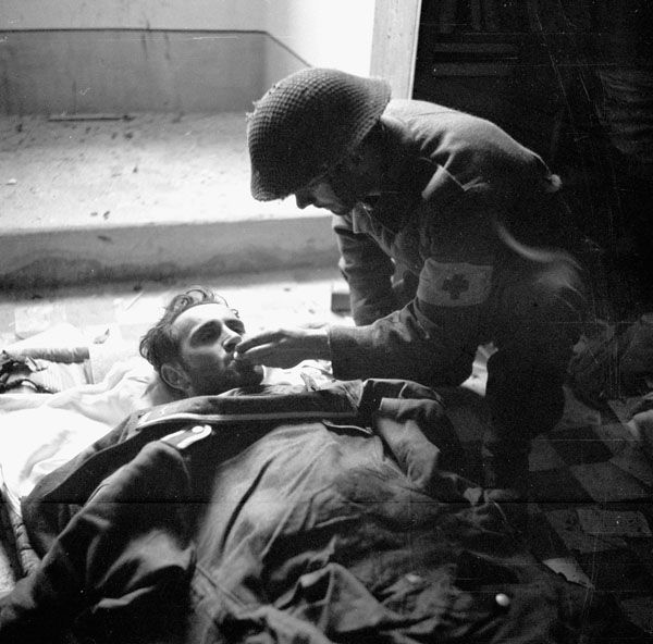 Pte. B.D. Flynn of The Seaforth Highlanders of Canada giving a drink of water to a badly-wounded German prisoner inside a church, Ortona, Italy, 21 December 1943.