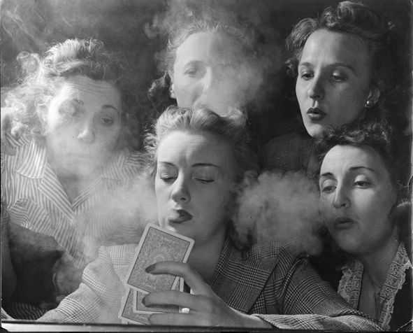 """Members of the Young Women's Republican Club of Milford, Connecticut, explored the pleasures of tobacco, poker, the strip tease, and such other """"masculine"""" enjoyments. Here, the women play poker and smoke."""