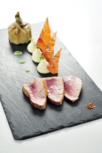 Gebraad van Columbus varkensvlees, een charlotte van aardappel en witloof, een mousseline van kervel en chips van ham
