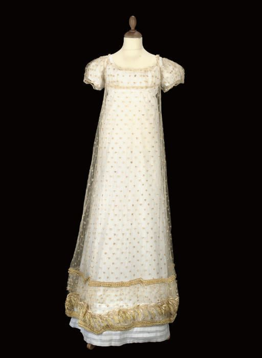 Lot 120 - A RARE IVORY TULLE STRAW-EMBROIDERED GOWN, CIRCA 1820  with simple fall-fronted bodice, the ground sprigged with straw stars and worked with a deep hem of straw and blown glass beadwork ears of corn, shown here worn over Lot 119 - Christies