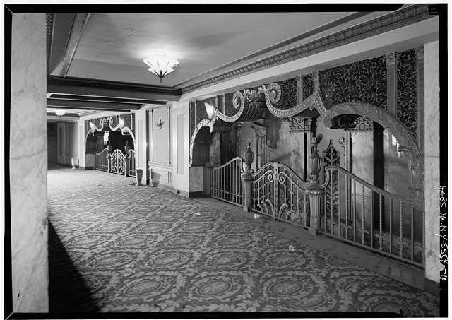 Step inside a seriously opulent Brooklyn cinema of old. It has tile flooring, ornate carved walls, decorative balcony rails, arched openings, gold accents, and ultra-high ceilings.