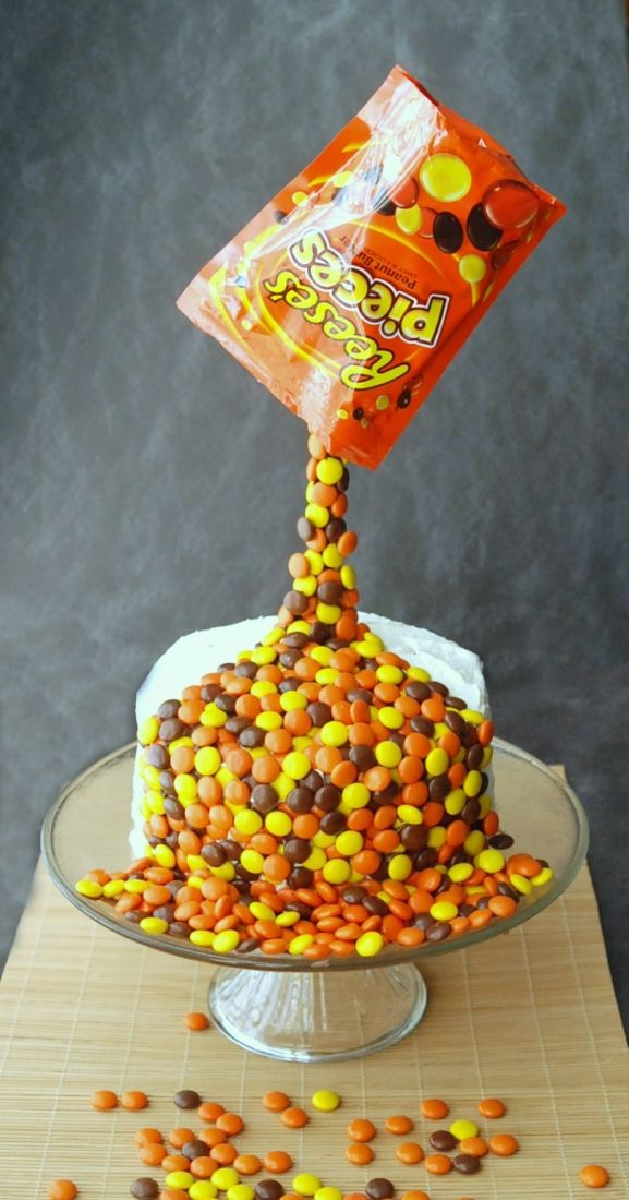 Learn how to make this amazing anti-gravity cake that looks like a bag of Reese's Pieces is being poured over the cake!