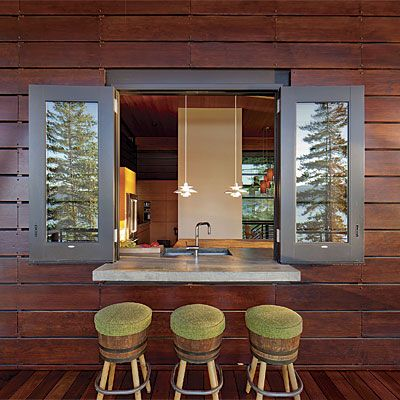 Home Remodeling Design: Cantilevered Connection: The 5-ft.-wide by 5-1⁄2-ft.-tall window, which is actually a modified storefront door, sits atop a poured-in-place concrete countertop that cantilevers over the adjacent deck space. The resulting outdoor bar space has room for three people