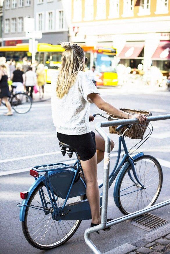 Girl riding a bike through the streets of Copenhagen, Denmark
