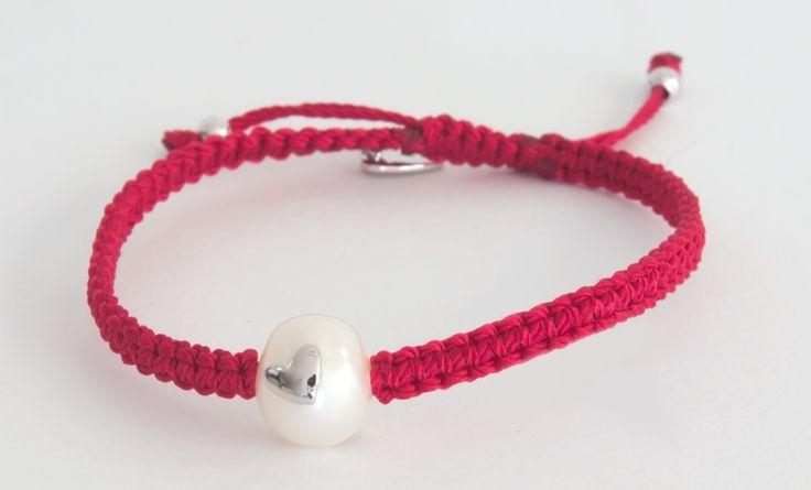 Pulsera tejida en macramé de color rojo con incrustación en plata con forma de corazón sobre perla blanca.