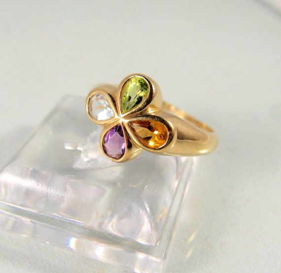 This beautiful ring is made out of 18K solid gold* and features four bezel set, faceted natural semi-precious gemstones. The stones are all natural and of high quality with no inclusions. They are pear shaped and set in a clover design. They include an amethyst, an aquamarine, a citrine and a peridot. All four semi-precious tones are loupe clean and extremely fine. This tutti frutti ring is very attractive and has a substantial feel about it (5 grams). It is in excellent condition and comes…