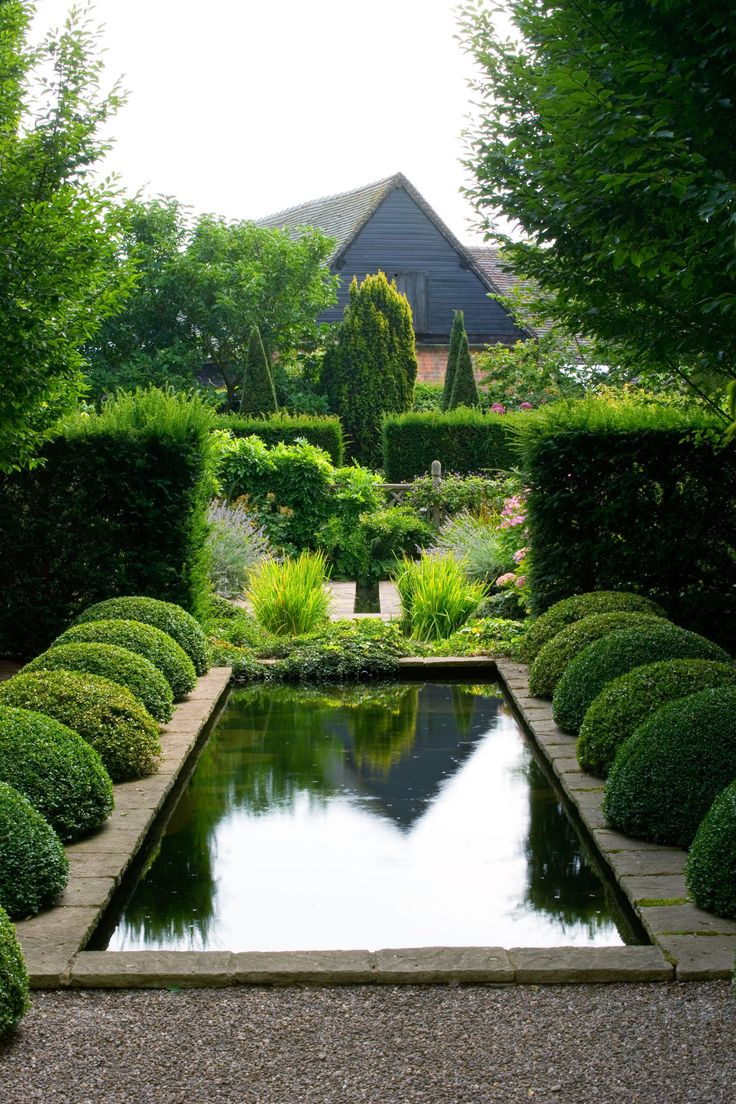 garden pond - love the small domes of box spilling over hard landscaping.
