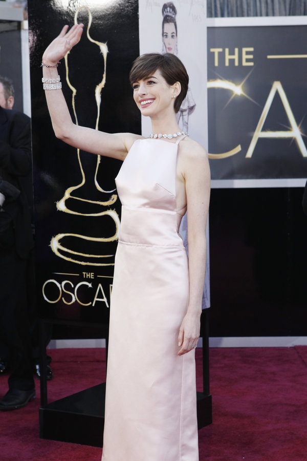 Anne Hathaway in Prada, pale pink gown, jewelry by Tiffany & Co. Red, pixie cut, Carpet 2012, Oscars 2013