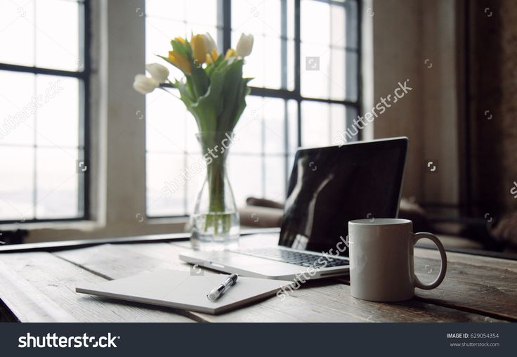 Feminine workplace with laptop mock up, coffee mug, bouquet of tulips, books, globe and empty page with pencil. Creative concept. Blogger's decorated workspace in front of big window.
