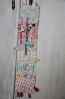 Jeden z mnoha šitých dárků pro děti. Sponkovník se spoustou našitých šňůrek a tkaniček pro nacvakaní sponek, s našitými poutky na provlečen...