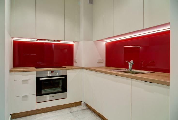 Aranżacja kuchni z mocnym akcentem kolorystycznym w postaci czerwonego backspalshu. Białe fronty szafek i drewniany blat kuchenny utrzymują całą kuchnię w minimalistycznym stylu.