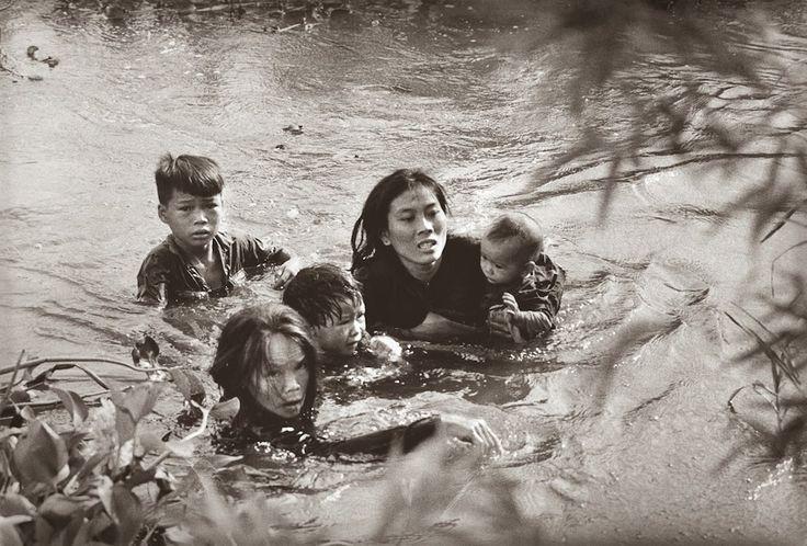 Uma mãe atravessa um rio com seus filhos em fuga a um bombardeio dos Estados Unidos, 1965.
