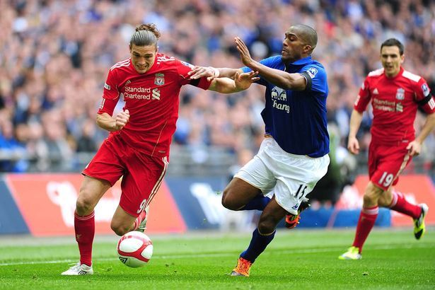 Andy Carroll and Everton's Sylvain Distin (centre) battle for the ball in 2012