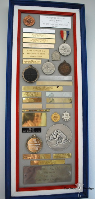 putting vintage metals and plaques on display in an old frame. Great idea to use for Braden's trophy plaques