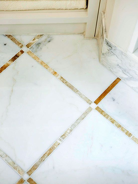 Golden-tone onyx tiles, which echo the color of the cabinetry, combine with crisp white marble to add a subtle layer of pattern to the bathroom floor. Radiant floor heating keeps the tile feeling toasty all year round.