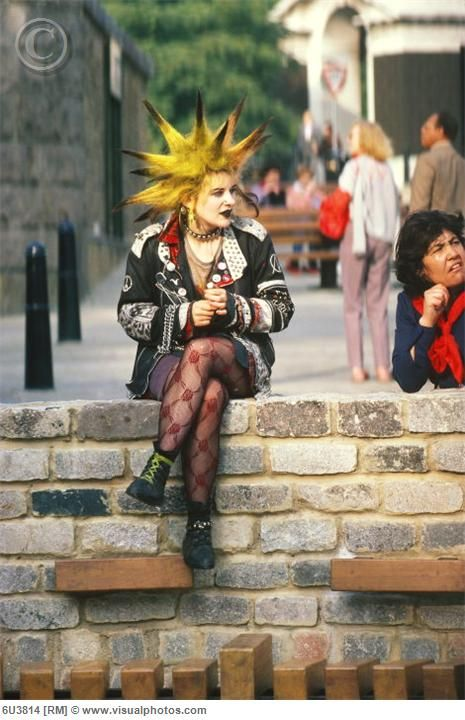 Female punk on wall with yellow and black spiked hair