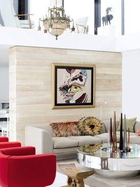 El salón, en dos alturas, cuenta con novedosos elementos arquitectónicos, como el panel de madera de saligna  blanqueada  o la estrecha abertura que se eleva en vertical hasta la planta superior. Sobre la chimenea, una artística composición de espejos refleja la colorista obra de Alexis Preller, colgada en el panel de madera. La mesa de espejo y la lámpara de techo proceden de Mila; y el taburete, de la etnia africana Ashanti, fue adquirido en Amatuli Fine Art