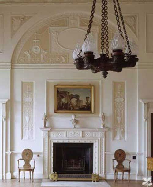 Robert Adam design - part of the Adams Brothers team who embraced the elements of Neoclassicism while paying homage to Greek and Roman cultures of antiquity. Note the symmetry and the high arch above the fireplace. The dimensional decorative wall elements relied heavily upon natural motifs like fruit, foliage and florals, mixed with icons and symbols of the ancient world. Truly timeless!