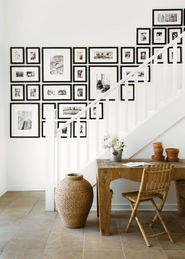 consistent use of black frame & white mounting, black + white photography, linear arrangement against a diagonal stair rail in white