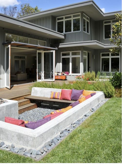 Lowered Outdoor Firepit with concrete sofa, bright-colored pillows and a river rock border.