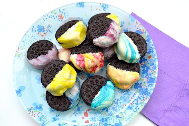 Oreos Tie & Dye. De délicieux biscuits au chocolat et à la poudre de lait enrobés de chocolat au lait et mis en couleurs par des colorants alimentaires.