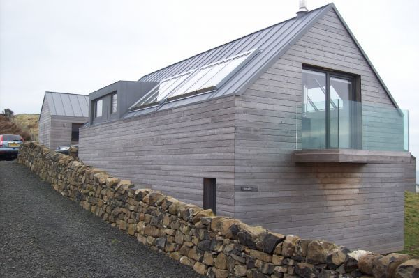 Crisp contemporary new build with scottish larch cladding, roof lights and frameless glass balconies