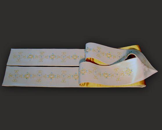 Stola sacerdotale bianca, realizzata in pregiato tessuto di seta shantung.  Questa stola liturgica presenta su tutta la sua lunghezza un delicato ricamo realizzato con filato laminato color oro giallo e oro bianco su cui sono applicate a mano cristalli azzurri e perle.