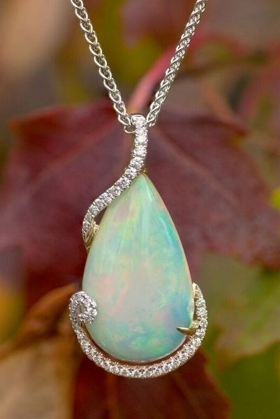 Elegant solid Australian opal with diamonds in white and yellow gold.  Visit us online at www.goldrushfinejewelry.com