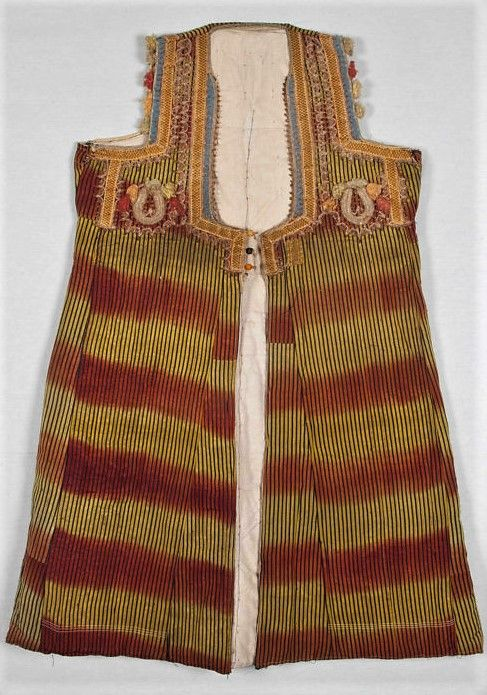 Traditional sleeveless caftan for women, from the Bartin region, ca. 1960.  Sometimes called 'uzun yelek' (long vest) or (locally) 'uskuta'.  Made of an ikat fabric; quilted and lined with white cotton.  The neck and upper front part are adorned with cotton & metallic thread embroidery and golden braid; the armholes additionally feature (small) multi-coloured tassels.  Size: 111 x 61 cm.