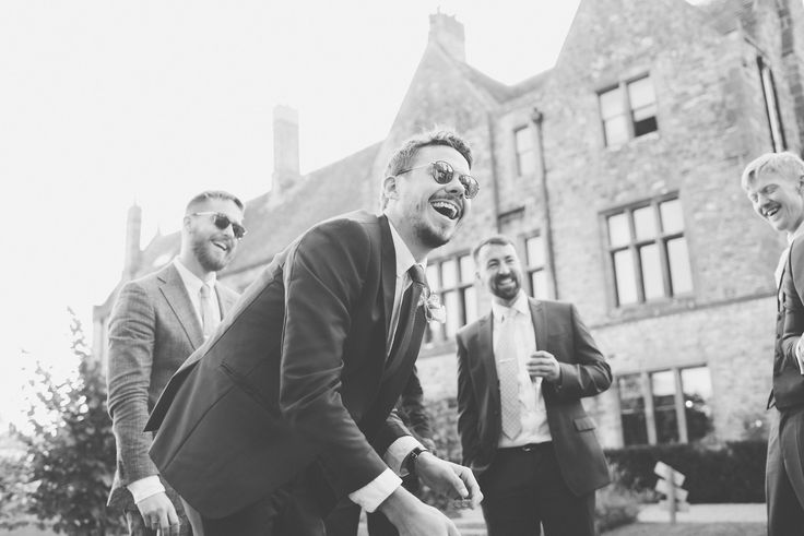 A black and white photo of wedding guests wearing shades in the sun.