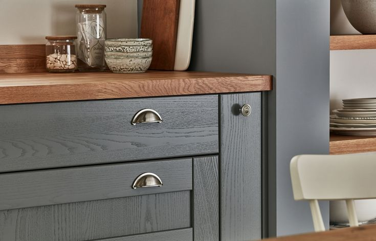 Brushed nickel effect handles add metallic highlights, while the use of a warm oak block worktop brings some natural character to the space. Visit our website to find out more about our full range of handles.