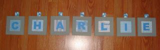 Lifeonthewink: projects-for the wall over grandsons crib. small wood frames from ac moore, scrapbook paper with cardboard backing and cardstock letters that i cut out. ribbon is attached with staple gun. small shiny nails with heads right through the ribbon (its strong ribbon and these are lightweight, so it should hold) hang them in a level line.