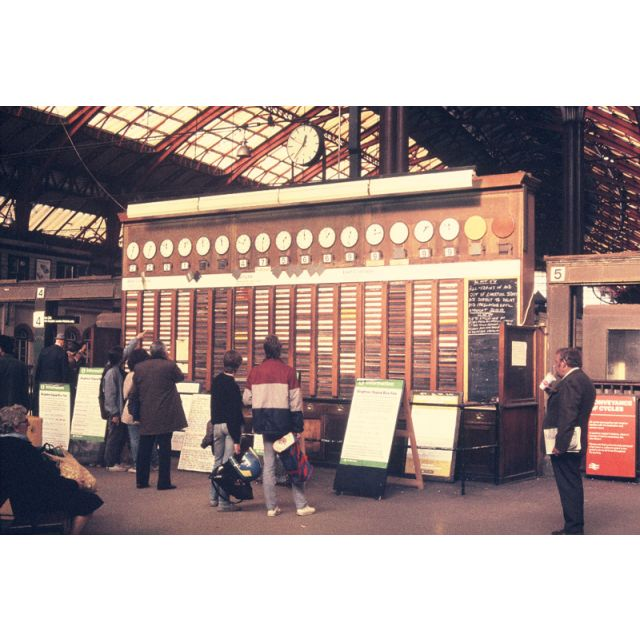 Train departure board shown in an archive photograph of Brighton Railway Station, UK.