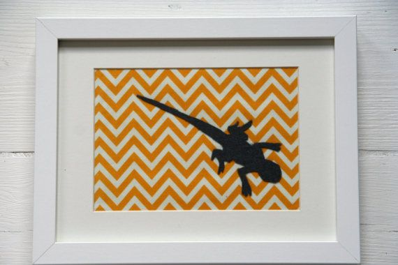Picture of a charcoal grey felt silhouette of a lizard on a vibrant yellow and white chevron fabric in a simple white frame.