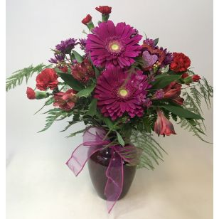 This design features mini gerbera, carnations, roses, alstroemeria, and garden flowers arranged in a red rose vase with a bow.