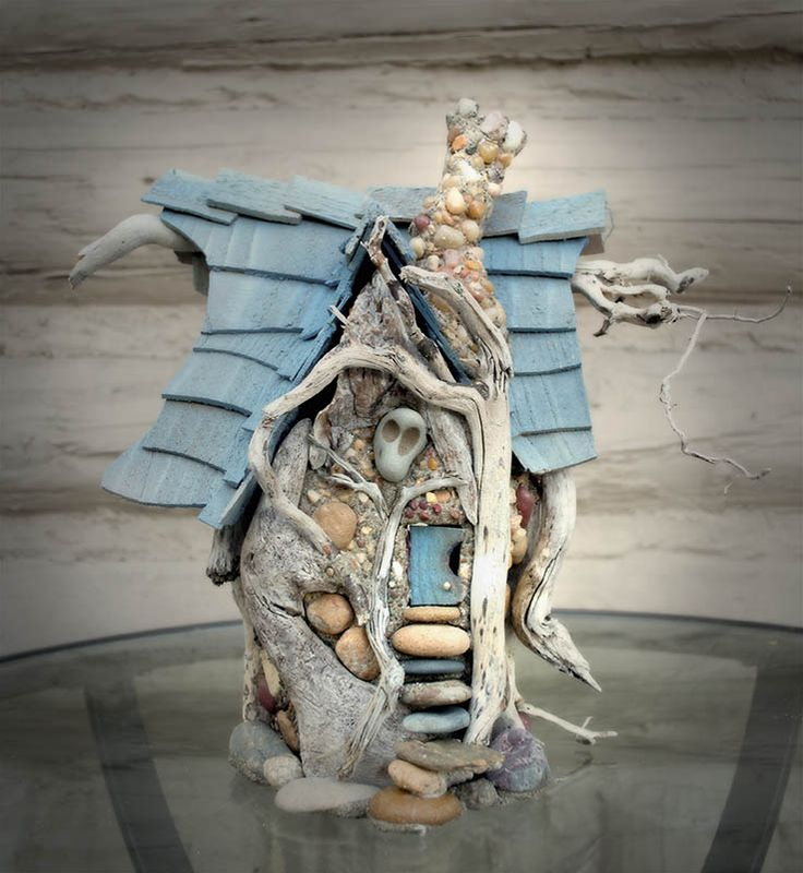 Well guarded by a Dramian nature spirit, this fairy house is full of quirks. A bendy chimney, a door that swings out with a very large hole in it and a cascade of stone steps. Lovely pallet of blues and rusty beiges.