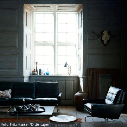 Wohnzimmer mit Sitzmöbeln aus schwarzem Leder | roomido.com