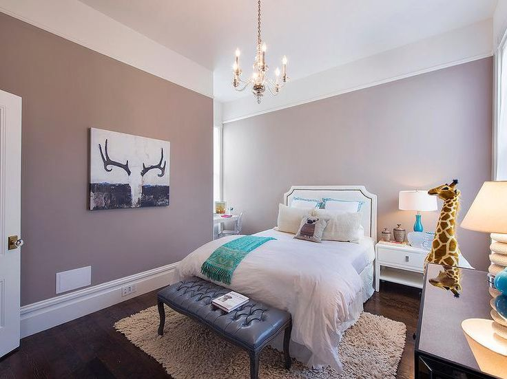 White and mauve teen girl's bedroom features walls painted Benjamin Moore Seaside Sand lined with white headboard accented with brass nailhead trim placed next to a single nightstand, West Elm Niche Nightstand and a turquoise blue lamp.