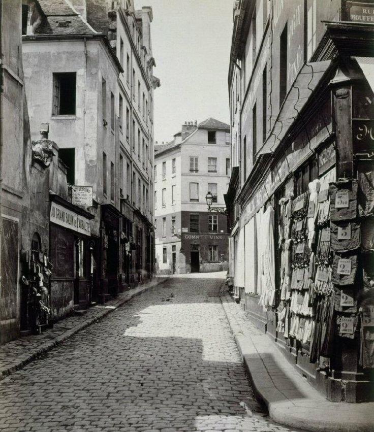 Une vue de la rue de l'Arbalète entre la rue Mouffetard et la rue Lhomond (rue des Postes avant 1868). Au Grand Salon de l'Arbalète, un salon de coiffure, la barbe simple coûtait 10 centimes. Une photo de Charles Marville, entre 1865 et 1867.