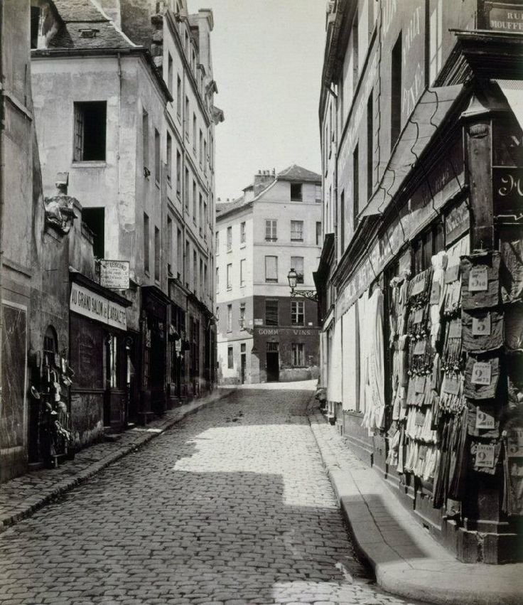 Une vue de la rue de l'Arbalète entre la rue Mouffetard et la rue Lhomond (rue des Postes avant 1868). Au Grand Salon de l'Arbalète, un salon de coiffure, la barbe simple coûtait 10 centimes. Une photo de Charles Marville, entre 1865 et 1867.
