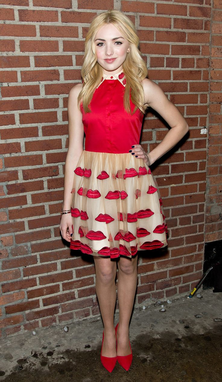 The young actress wore a spirited dress covered in kiss-shaped appliqués at the Alice + Olivia presentation.