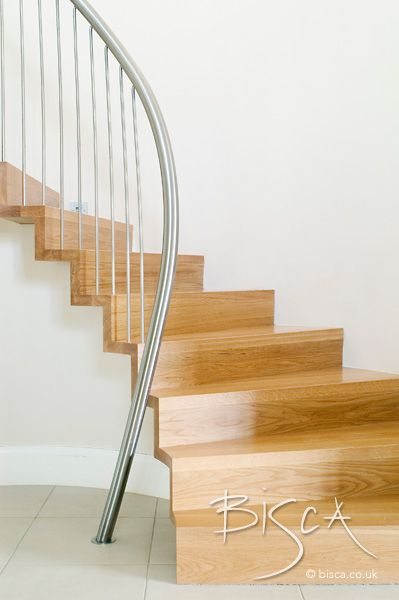 A curved oak staircase designed for a curved alcove in an entrance lobby. The semi cantilevered staircase is built of oak and steel and the design is rather unusual, in that it starts as a full width stair at the foot, but the treads become deeper set into the wall as the stair climbs to first