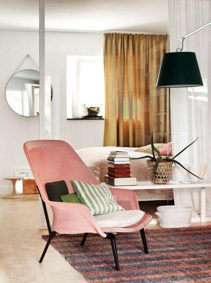 Bakom glasväggen i vardagsrummet ligger Hans och Hannes sovrum. Den rosa fåtöljen är en Slow Chair, design Ronan och Erwan Bouroullec, Vitra. Bänk av Alvar Aalto, Artek, och golvlampa från Artemide. Spegeln i bakgrunden kommer från Hay. Petra-Bindel