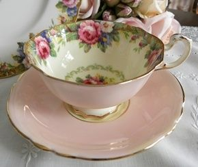 pink and white Teacup and Saucer with floral decor inside cup, all trimmed with gold