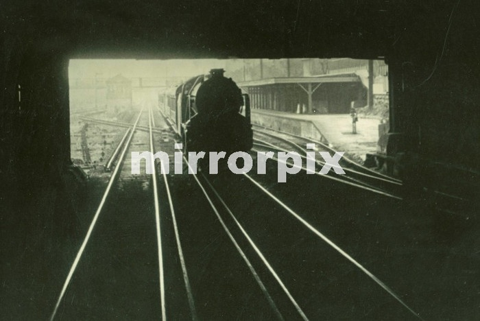 Steam Engine pulling out of unknown station under a bridge.