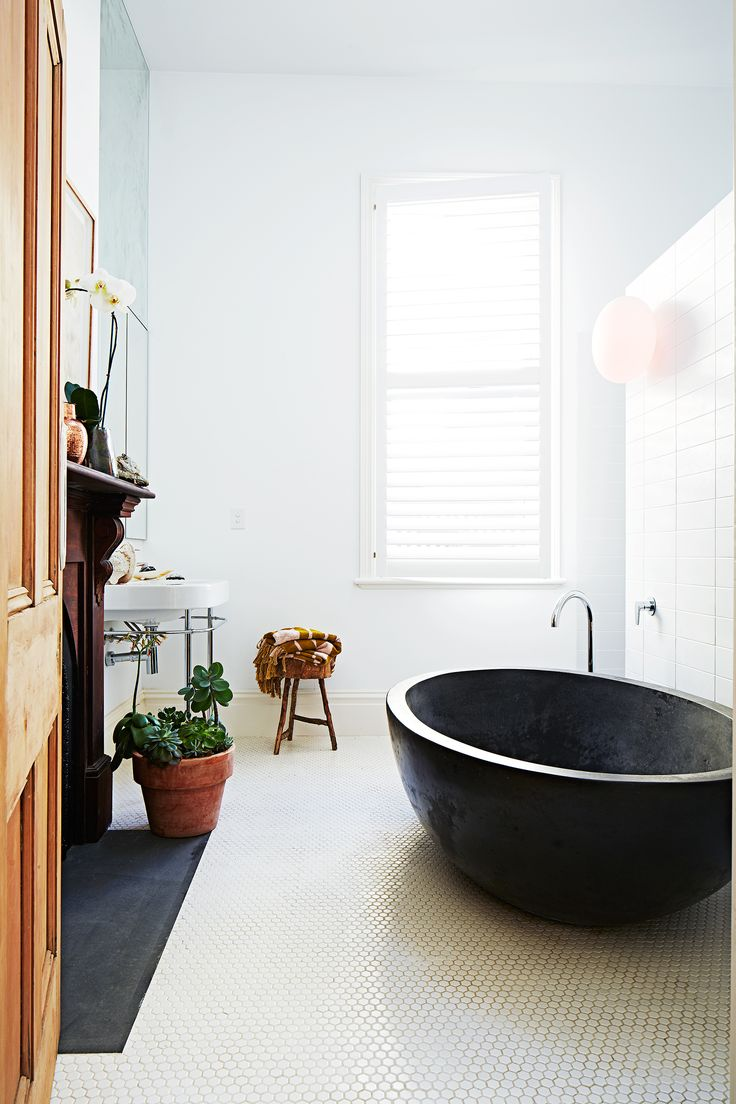 The former living room of this renovated Victorian terrace house was converted into a large family bathroom featuring a concrete bath by Boyd Alternatives and matte white tiles from Perini. Photography: Diana Pritchard | Styling: Amber Lenette